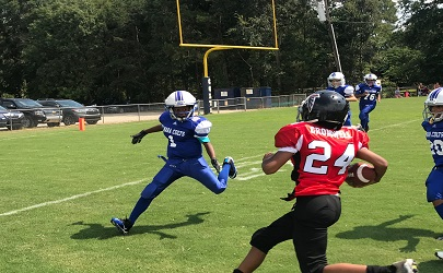 An opposing player about to be tackled by a MARA Colts Football player during a game